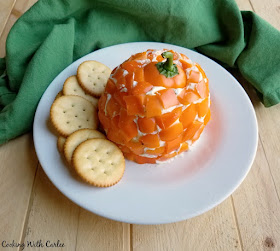 Havarti cheese ball coated in orange bell pepper pieces with the top of a bell pepper on top as a pumpkin stem with crackers on a plate