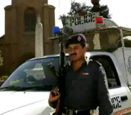 A Pakistani policeman carrying a gun