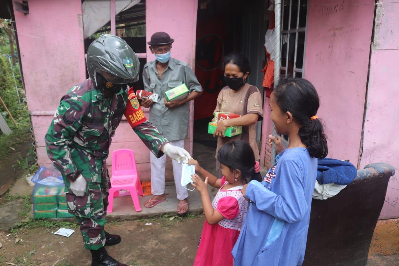 Sejumlah personel Babinsa Koramil 410-02TBS Kodim 0410KBL sambangi warga dalam rangka berbagi nasi kotak dan masker gratis di wilayah binaannya