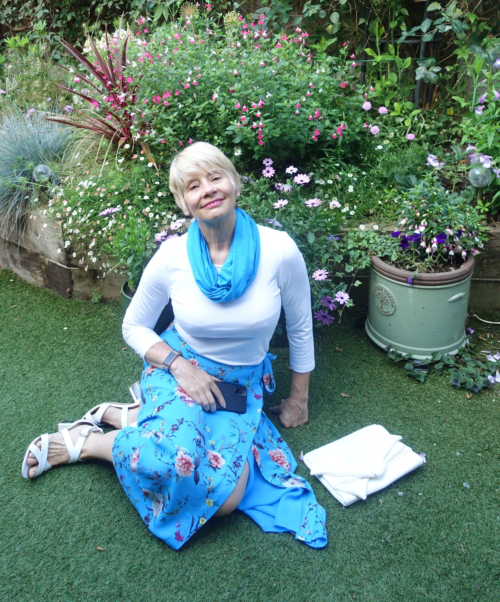 Look good over 50. Gail Hanlon from Is This Mutton in floral skirt with white top, 40s style sandals and Chinese Blue infinity scarf