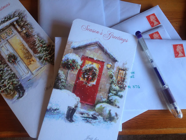Christmas Cards scattered with envelopes and stamps, pen