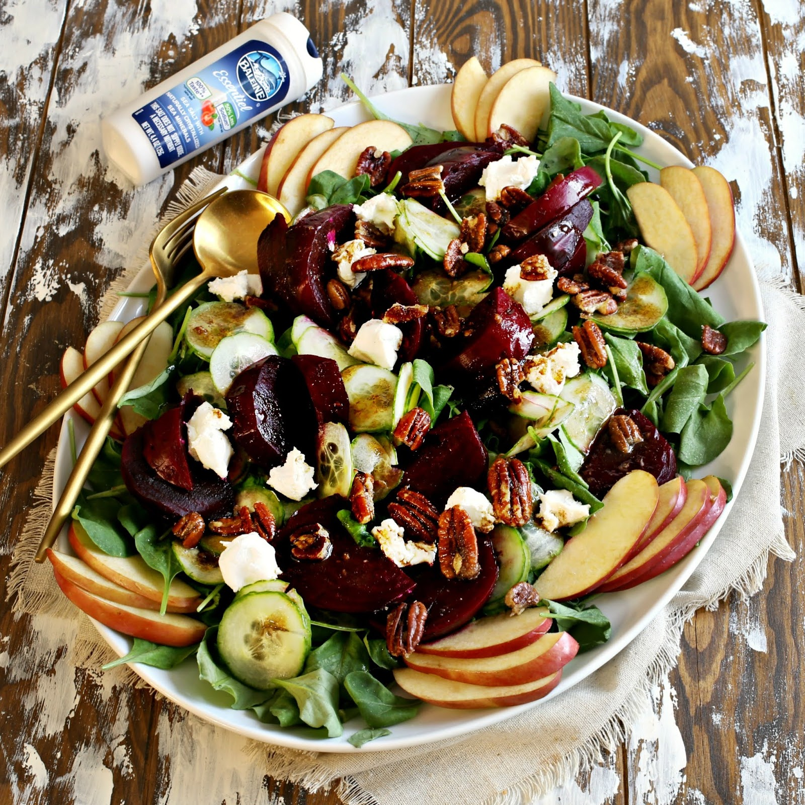Recipe for a crunchy vegetable salad with arugula, apples, cucumbers, beets, goat cheese and candied pecans.
