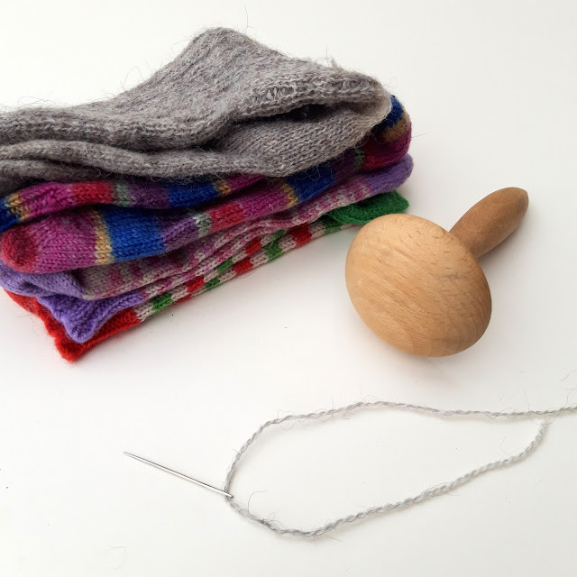 A pile of multi-coloured socks waiting to be mended.  In the foreground are a wooden darning mushroom and a length of yarn on a needle.  All against a white background