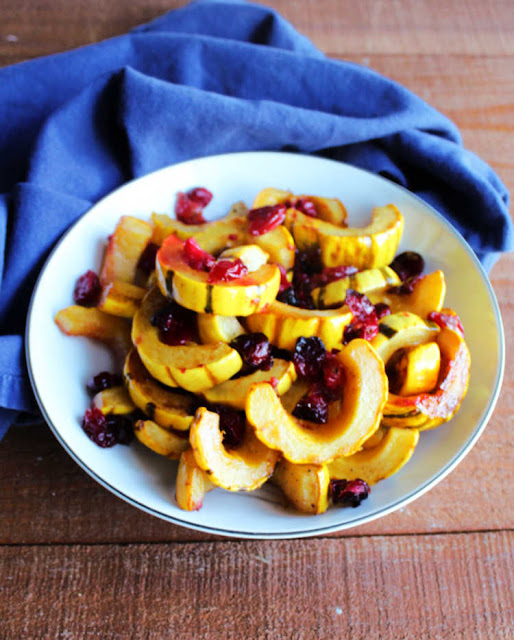 bowl of roasted slices of delicata squash and cranberries