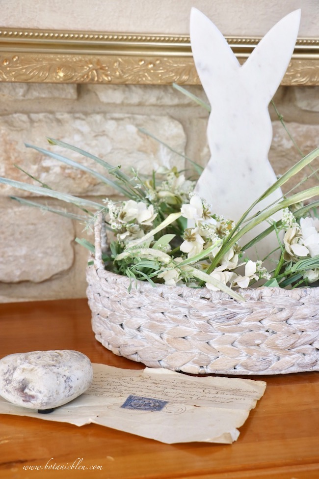 Beautiful Spring Centerpiece with marble bunny, faux flowers, and white-washed basket