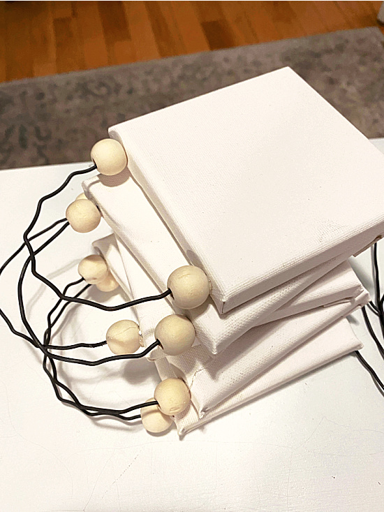 stack of canvases with wires and beads