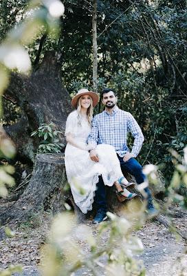 couple sitting on tree stump smiling