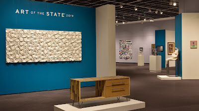Exhibit gallery with blue and white walls, paintings on walls, sculpture and furniture on pedestals