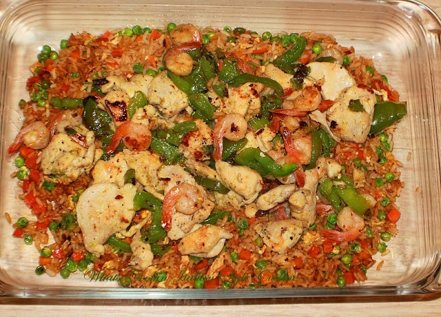 this is a glass casserole dish with  stir fried chicken and shrimp with broccoli and peppers.
