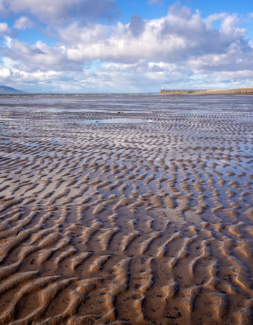 Photo of patterns in the sand looking towards Maryport Pier
