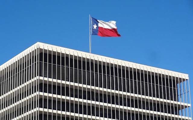 Texas flag flying atop HCC Admin Building