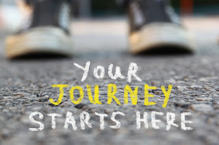 """Image with selective focus over asphalt road and person's shoes with handwritten text - """"your journey starts here"""""""