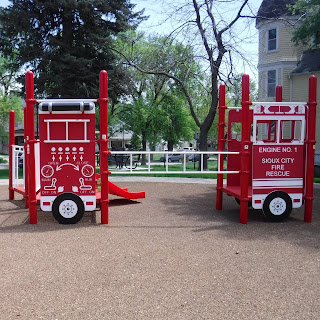 a red play structure with a fire truck theme at Rose Hill Park