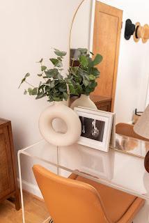 white modern donut vase with eucalyptus on desk
