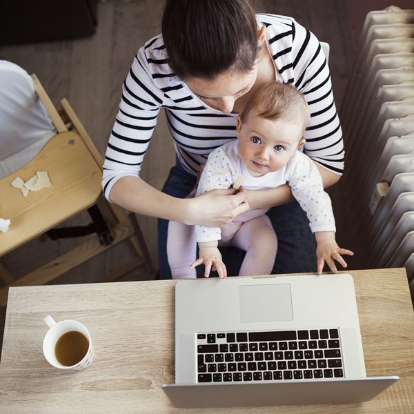 Mother working at computer with baby in arms