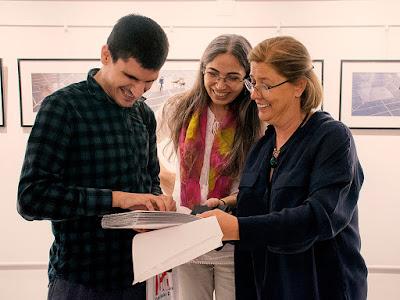 Fotoğrafta Kentin Merkezine Seyahat fotoğraf sergisinin katalogunu Braille ile hazırlayıp açılışa getiren arkadaşımız Yusuf Ak, çizgelikedi'den Arzu Filiz Güngör ve serginin fotoğrafçısı Ayşen Ertango Özkaya birlikte gülüyorlar. Ellerinde büyük ve kalın bir katalog tutuyorlar.
