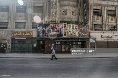 Egyptian walking an empty street outside a cinema house in Downtown Cairo during the Eid