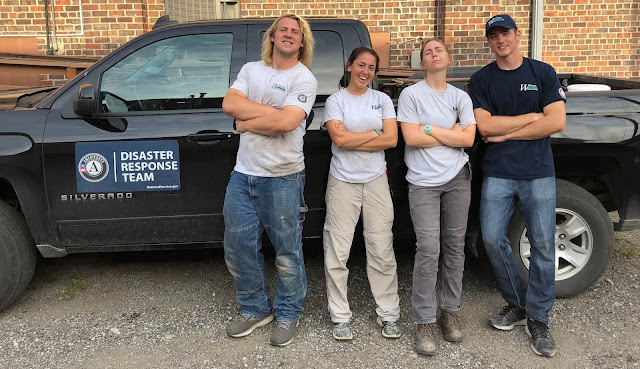Four AmeriCorps members, wearing shirts with AmeriCorps logos, stand in front of a blue truck crossing their arms.