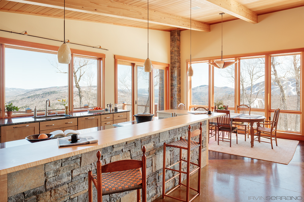 The long galley kitchen, designed Bethel Kitchen Designs, in a ski home in Maine overlooks a stretch of Grafton Notch, with the slope of Puzzle Mountain on the western side.
