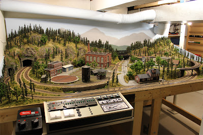 A completed 4 x 8 HO scale model railroad layout set in a mountain forest scene with a control panel