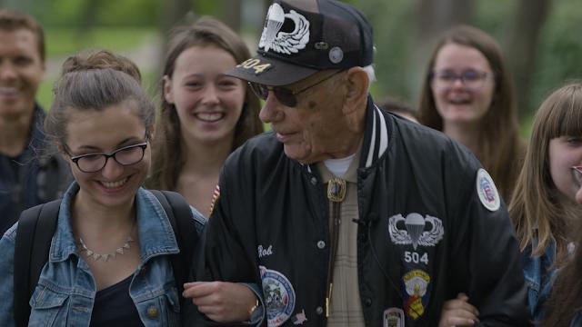 A crowd of teenage girls gather around an oldder veteran