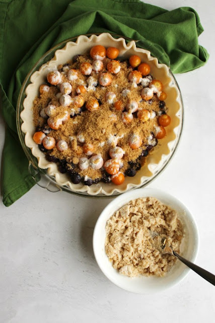pie shell filled with fruit sprinkled with brown sugar and flour with a bowl of crumble topping