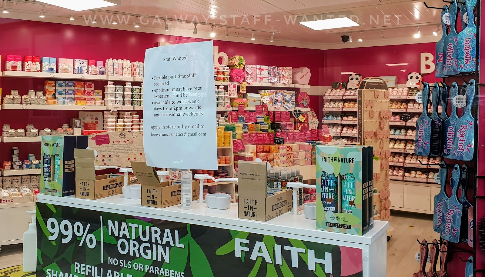 Shop window display with a job advert and a display of 99% natural origin - no sls or parabens - Faith in Nature beauty products