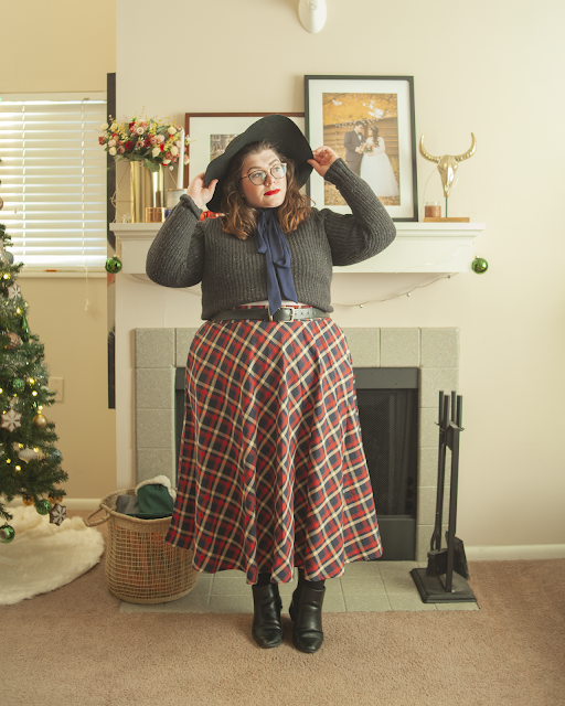 An outfit consisting of a wide brim black hat, a grey sweater over a red, blue and white plaid skirt, a blue ribbon around the beck and black Chelsea boots.
