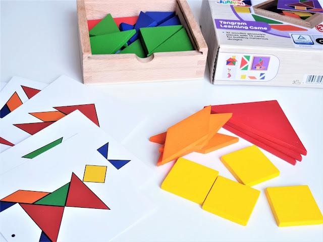 na zdjęciu widać układankę Tangram - pudełko, elementy w różnychy kształtach i kolorach oraz karty do odwzorowania