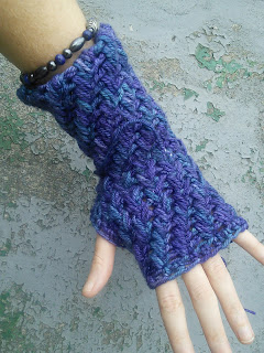 Someone wearing a fingerless mitten done in a spiralling textured crochet stitch.  The yarn is a variegated blue-purple, and there are yarn ends still hanging from the mitten.