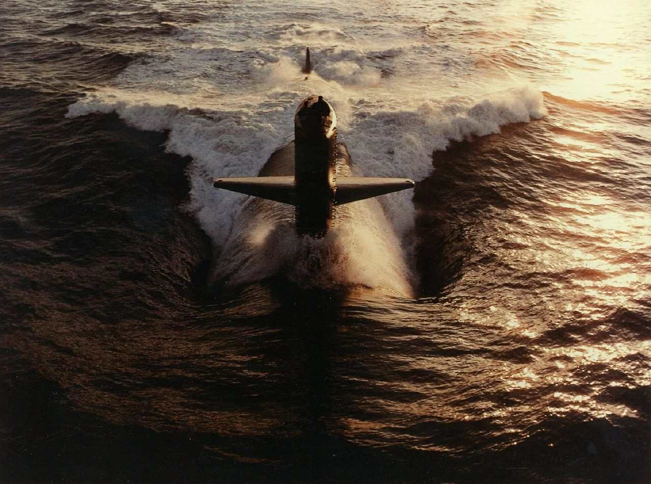 submarine cruises toward camera on the water surface for blog post about submarie movie thrillers