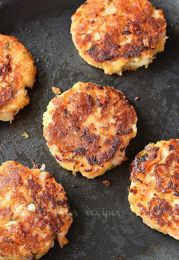 a birdseye view of a black skillet with cheesy shrimp cakes arranged