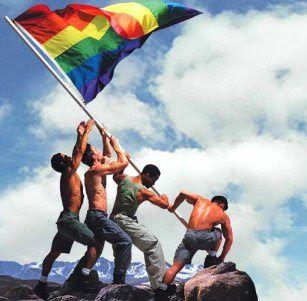 Cuatro hombres musculosos de pie sobre las rocas, levantando y a punto de clavar la bandera de orgullo gay que flamea al viento