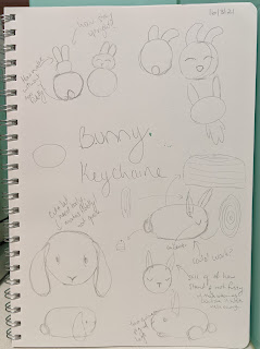 """A photo of an A4 art diary set up portrait which has pencil sketches of bunnies and toys with notes and scribblings. In the middle in large handwriting says """"Bunny keychain"""". One of the designs has been drawn at different angles with dissections for how it would be made."""