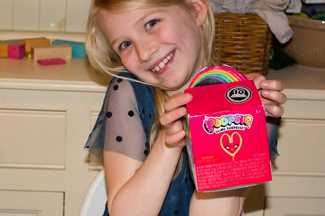 A girl pulling a slightly manic face and posing with the Poopsie Surprise Poop Pack box