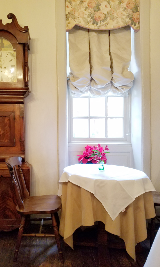 A charming spot by the window with balloon shade and old clock.
