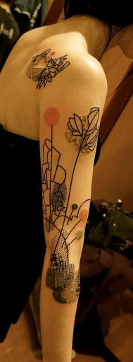 Um estilo de desenhos animados horizonte é retratado todo estilizado com flores enormes hastes que levam a uma série de padrões. A peça é retratada em preto e branco e colorido e é retratado na parte de trás do portador da parte superior do braço.