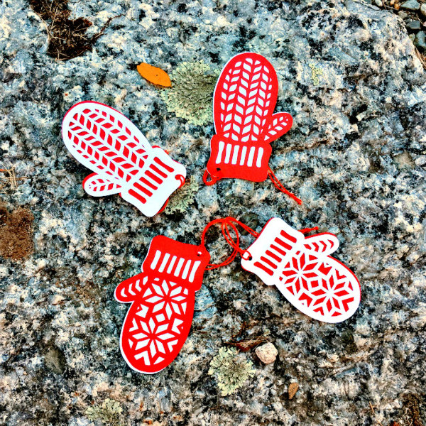 four red and white paper cut mitten gift tags