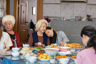 "Movie still for A24's 2019 film ""The Farewell"" where Awkwafina rests her head on her grandmother's shoulder at a dinner table full of people"
