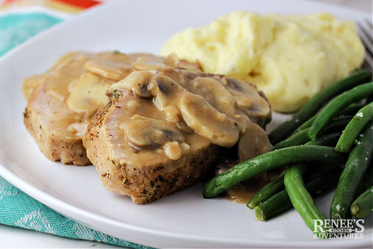 2 slices of pork ribeye roast with mushroom gravy on top on a white plate with mashed potatoes and green beans