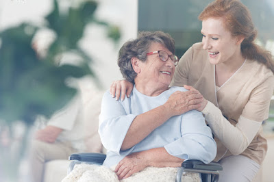A caregiver places her hands on an elderly woman's shoulders.