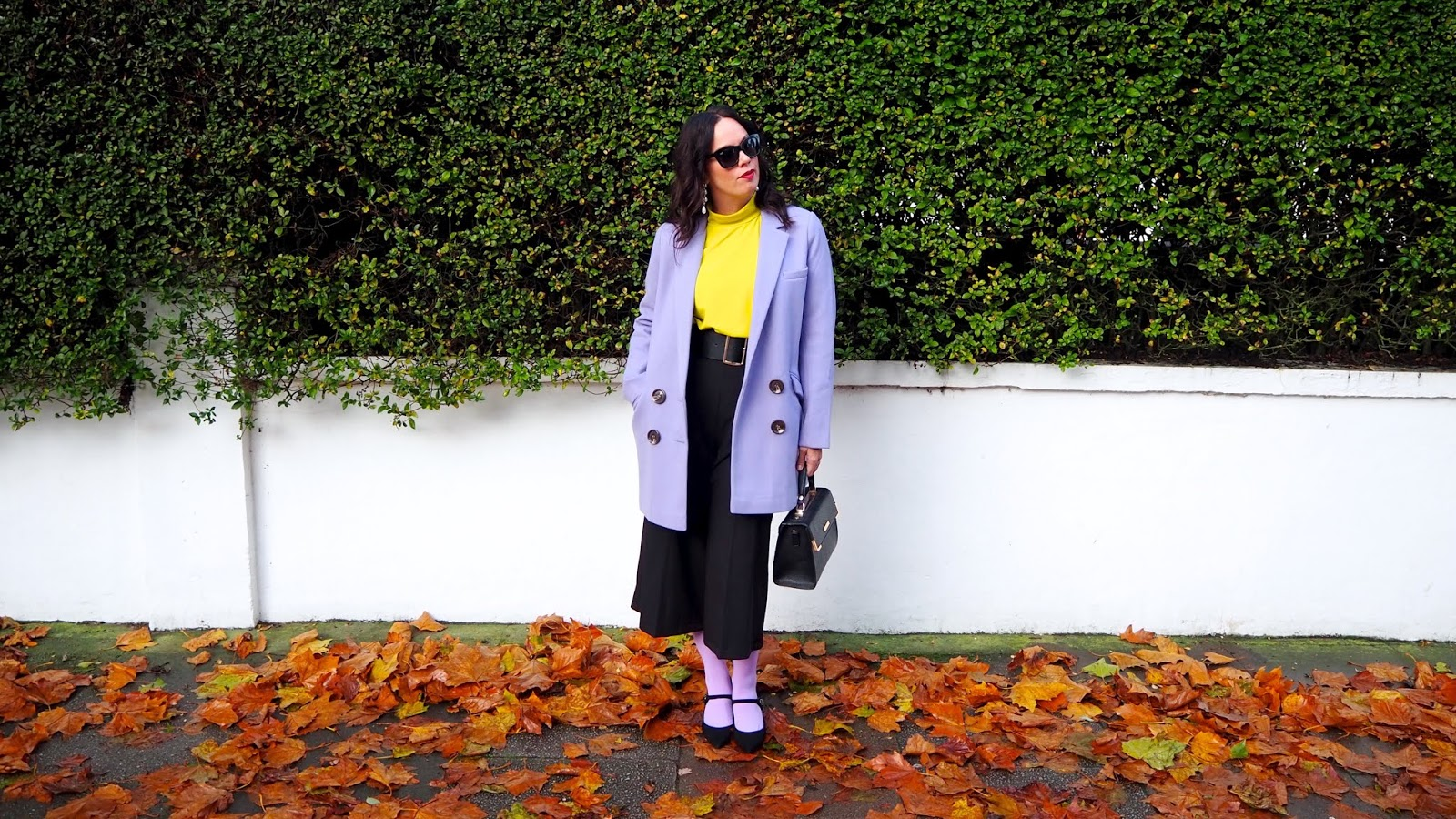Lilac double breasted coat with yellow blouse, lilac tights, black culottes and black maryjane heels