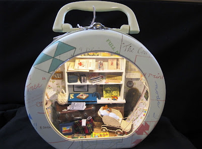 Small round metal suitcase with a clear front, containing a one-twelfth scale scene containing 1940s items.