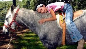 Equinoterapia. Niña montando y abrazando caballo