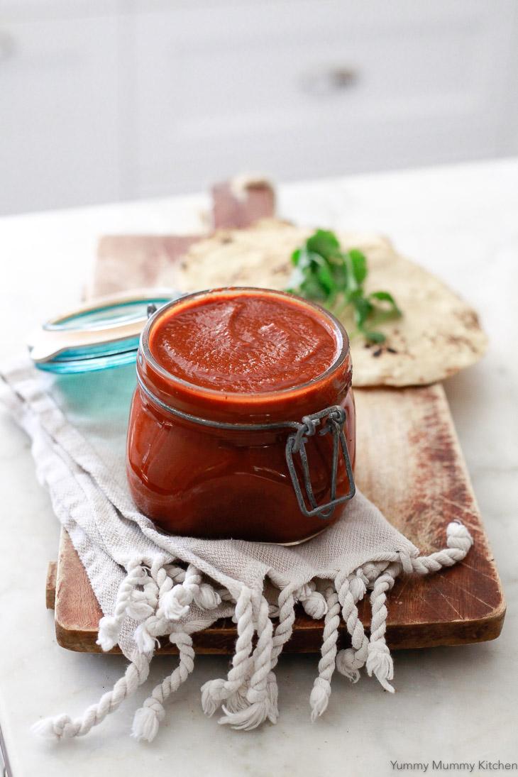 A glass jar of homemade enchilada sauce.
