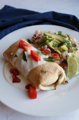 baked chimichanga with white queso, chopped tomatoes and cilantro on top served with Mexican rice, lime wedges and avocado slices
