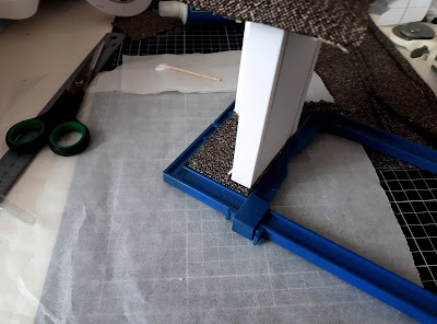 Work table with a half-made one twelfth scale modern miniature couch with clamps holding the fabric into one arm. in the background is a steel ruler, pair of scissors and a fabric cutter.