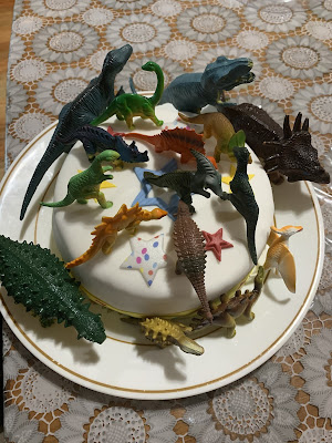 a birthday cake covered in toy dinosaurs