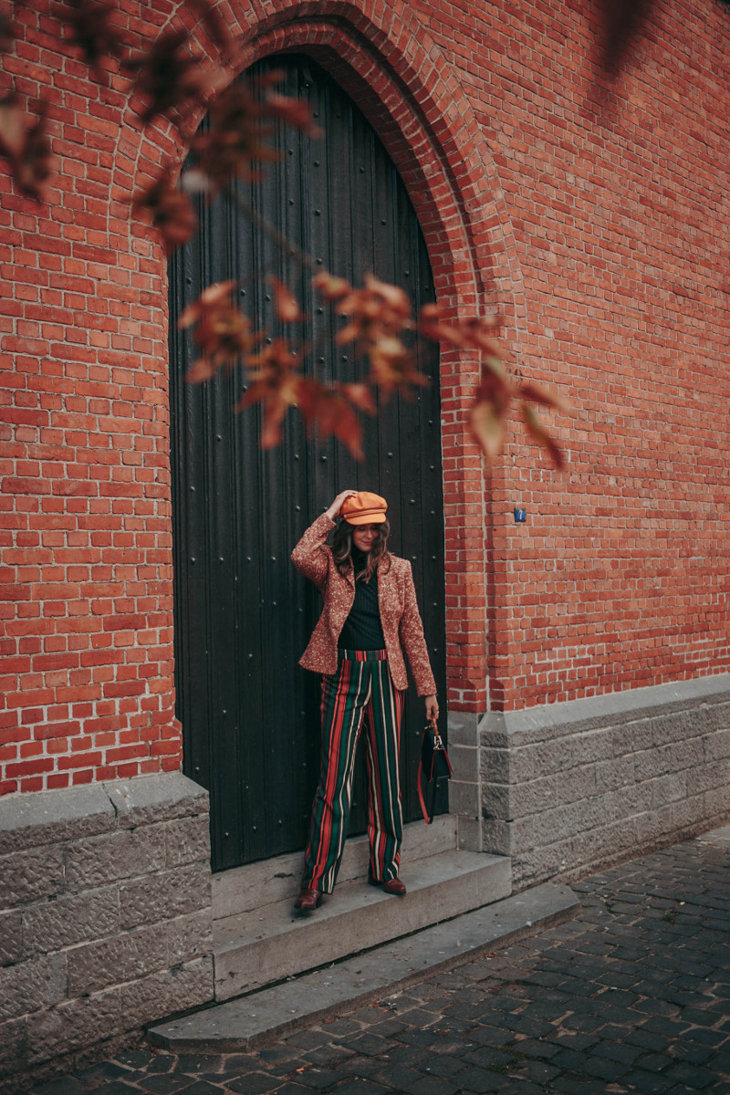 60s fall outfit with striped trousers and brixton cap