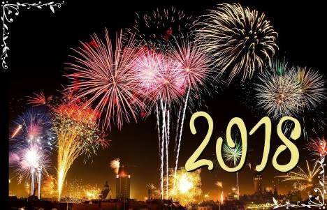 Paisagem de virada de ano com muitos fogos brilhando no ar e escrito, 2018.